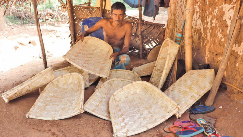 Senavirathna Banda with the winnowing fans he made.  Picture by  A.A.L. DIAS