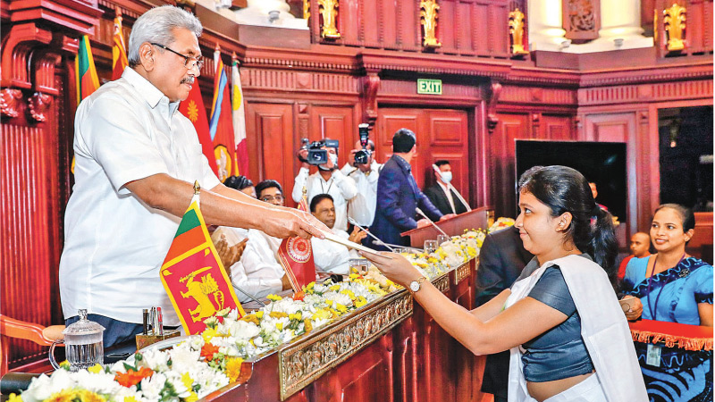 """President Gotabaya Rajapaksa handing over an Appointment letter to a graduate at the Presidential Secretariat yesterday evening under the Government's programme to recruit 60,000 graduates to the Government Service to build a culture of 'Working for the Country' as envisaged in the President's National Policy Framework, """"Vistas of Prosperity and Splendour"""".  Picture courtesy President's Media Division"""