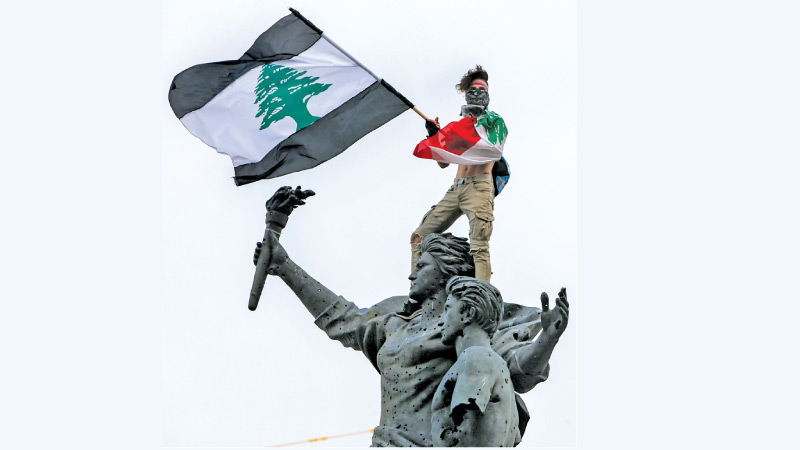 A demonstrator holding a Lebanese flag with black stripes stands atop the Martyrs' Statue at the Martyr's Square in the centre of Lebanon's capital Beirut on Tuesday. - AFP