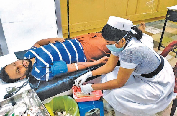 A Health Department official and donor  at the  blood donation camp