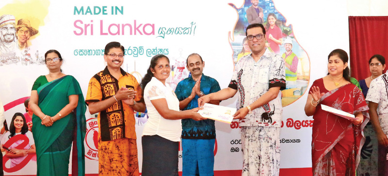 Chief Executive Officer/General Manager Ranjith Kodituwakku presents a loan to a female entrepreneur