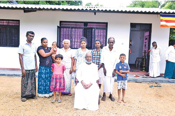 Somarathne with Tikiribanda and his family in front of their new house. Picture by M.A.R. Manukulasooriya