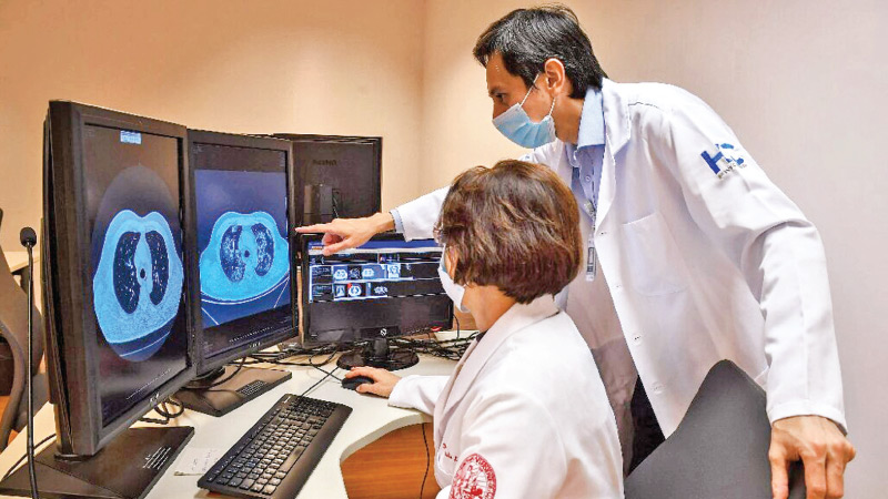 Doctors at the University of Sao Paulo Clinical Hospital in Brazil look at tomography images of lungs of virus victims in their fight against the COVID-19 pandemic.