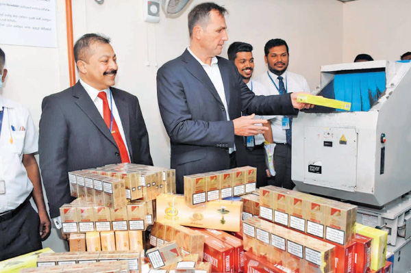 The illegal stock of cigarettes being destroyed by the officials at CTC crusher in the presence of Customs Director General Retired Major General Vijitha Ravipriya and company CEO Nadel Salem. Picture by Ranjith Asanka