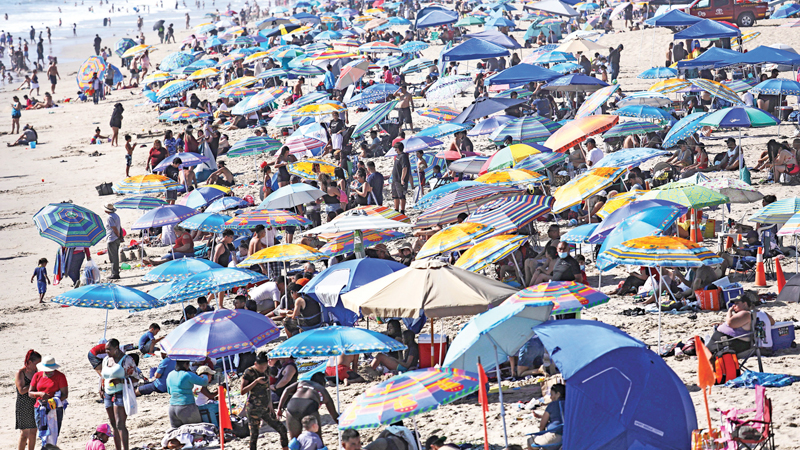 SANTA MONICA, CALIFORNIA - SEPTEMBER 05: People gather on the beach along the Pacific Ocean on the first day of the Labor Day weekend amid a heatwave on September 5, 2020 in Santa Monica, California. Temperatures are soaring across California sparking concerns that crowded beaches could allow for wider spread of the coronavirus amid the COVID-19 pandemic. AFP