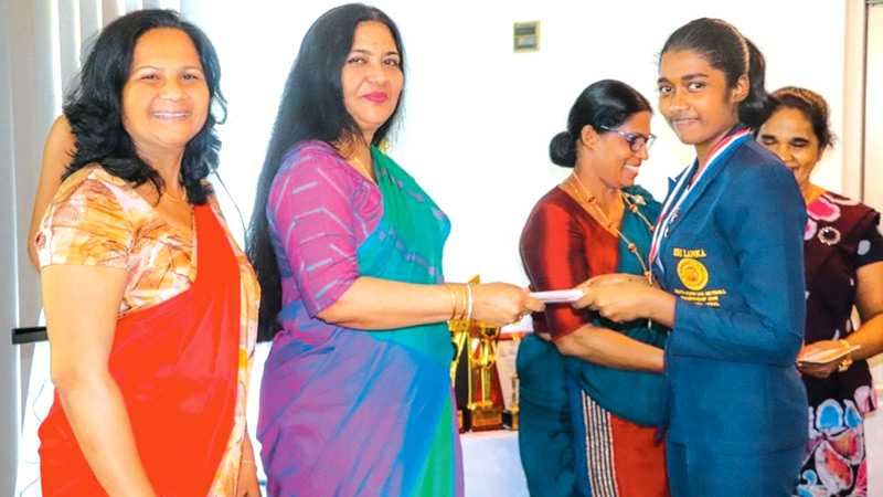 A member of the Sri Lankan champion under 16 netball team receiving her certificate from the netball president Lakshmi Victoria during the  felicitation ceremony held at the Cinnamon Lakeside Hotel recently. Sri Lankan junior head coach Amalka Gunatilleka is also in the picture.
