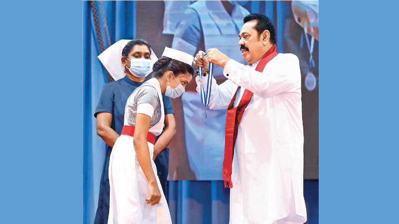 Prime Minister Mahinda Rajapaksa was the Chief Guest at the 'Capping Ceremony' of 298 newly recruited nurses to the State health sector who passed out from the Colombo Nursing School. The Prime Minister presenting a medal to one of the nurses during the ceremony held at Temple Trees yesterday. Picture by Sulochana Gamage