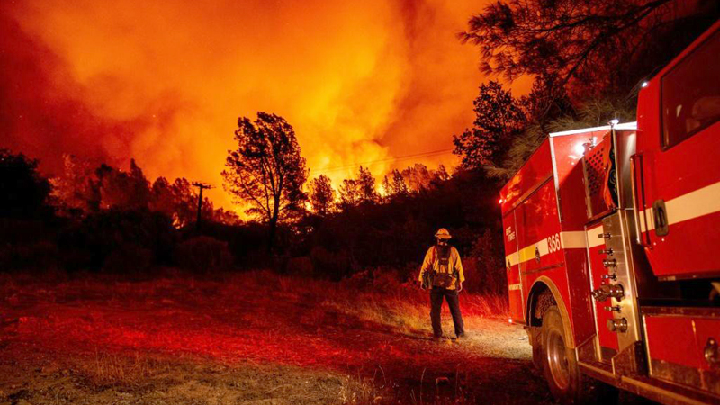 Butte county firefighters watch as flames tower over their truck during the Bear fire in Oroville, California.