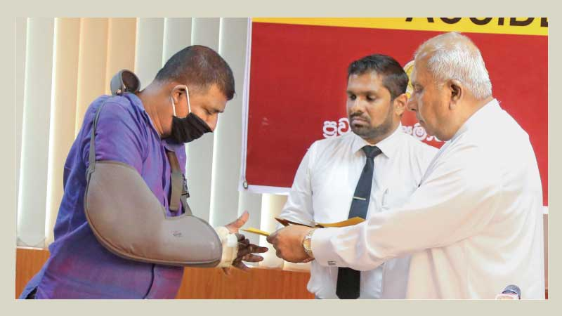 Transport Minister Gamini Lokuge presents a cheque as compensation payment.
