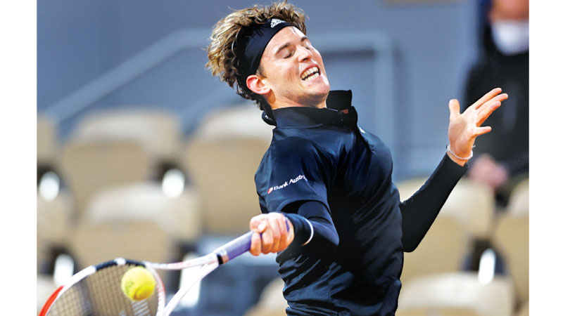 Austria's Dominic Thiem returns the ball to Norway's Casper Ruud during their men's singles third round tennis match on Day 6 of The Roland Garros 2020 French Open tennis tournament in Paris on Friday. - AFP