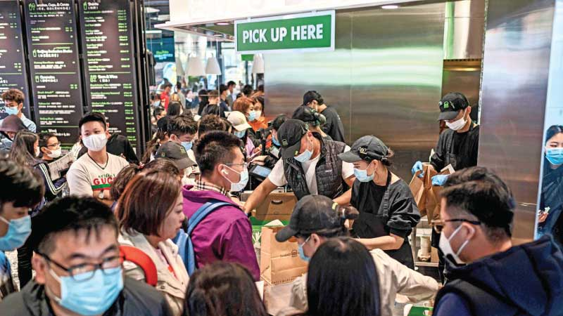 """People get their food inside a Shake Shack restaurant at a shopping mall during the national  """"Golden Week"""" holiday. - AFP"""
