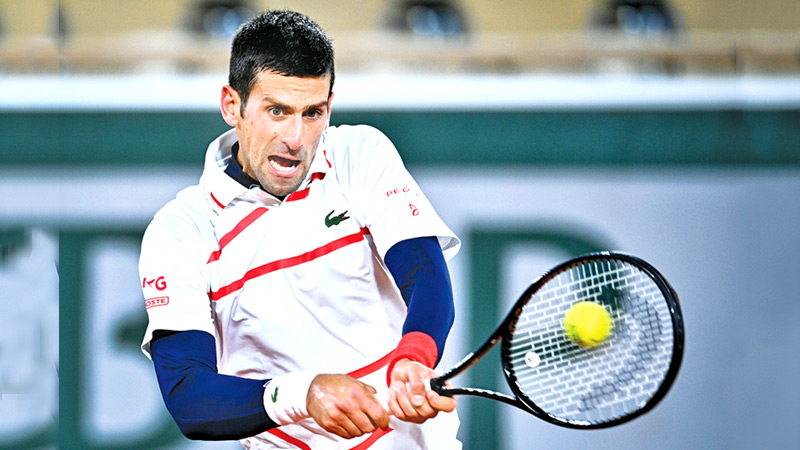 Serbia's Novak Djokovic returns the ball to Spain's Pablo Carreno Busta during their men's singles quarter-final tennis match on Day 11 of The Roland Garros 2020 French Open tennis tournament in Paris. AFP