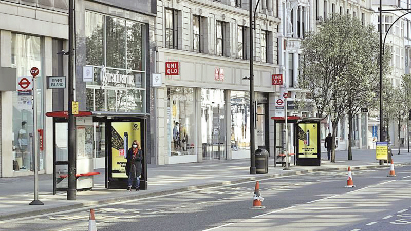 A woman waits for a bus on a deserted Oxford Street in London during the lockdown.