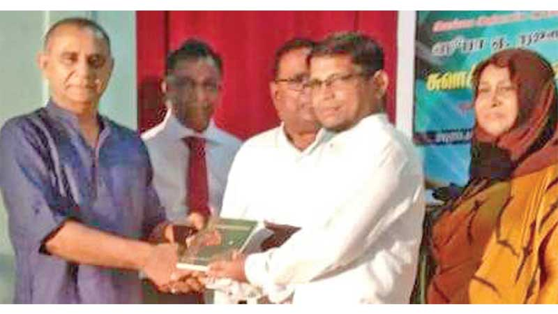 Poet A.R.Fathima Shoofa presenting the first copy of the book to the chief guest.
