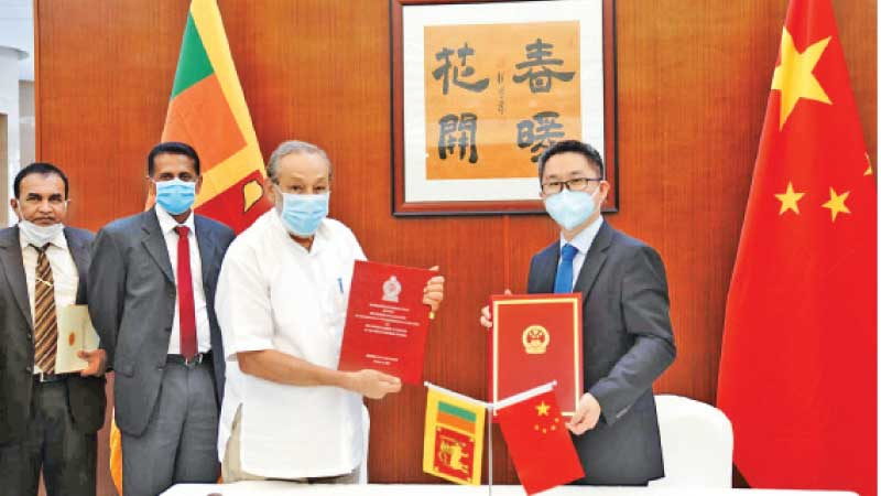 Chargé d'affaires of the Chinese Embassy in Sri Lanka Hu Wei and Water Supply Minister Vasudeva Nanayakkara yesterday exchanging document after signing a Supplementary Agreement to the MoU on water research and technology cooperation.
