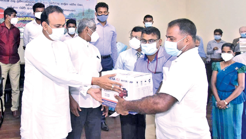 A planter receiving a water pump from Minister Dr. Ramesh Pathirana. Picture by Mahinda P. Liyanage, Galle Central Special Corr.