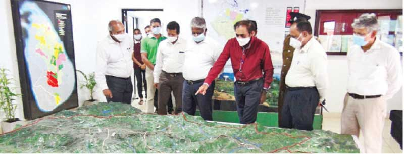 State Minister of Mahaweli Zone Canals, and Settlement Infrastructure Development Siripala Gamlath reviewing the map of the proposed project.