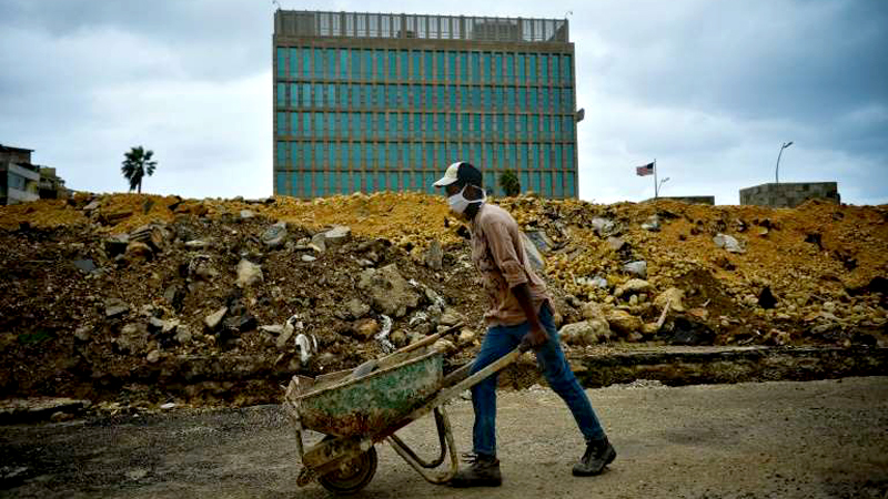 A construction worker pushes a wheelbarrow near the Embassy of the United States of America in Havana, which was closed by President Donald Trump.