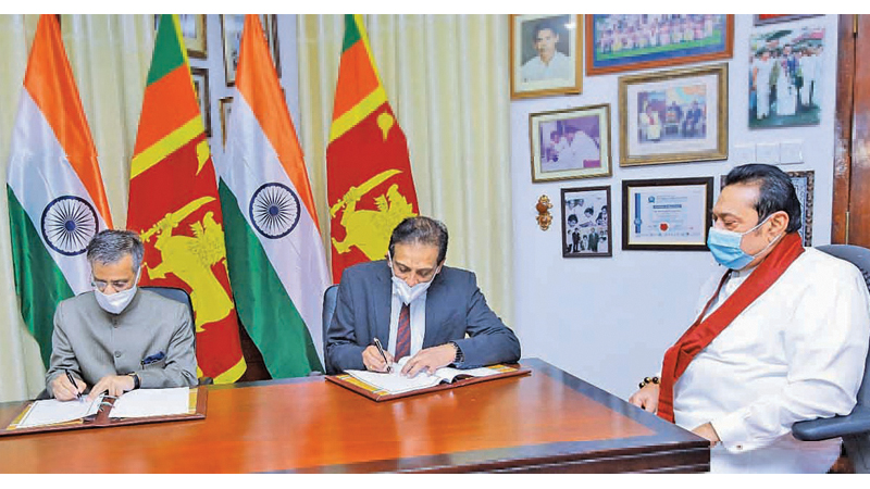Indian High Commissioner Gopal Baglay and Treasury Secretary S.R. Attygalle signing the Memorandum of Understanding (MoU) to implement High Impact Community Development Projects (HICDP) under Indian grant assistance in the presence of Prime Minister Mahinda Rajapaksa at Temple Trees on Tuesday.