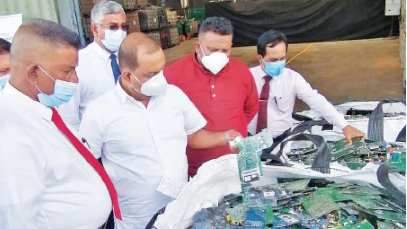 Environment Minister Mahinda Amaraweera and officials with the first consignment of electronic and electrical waste exported to Japan.