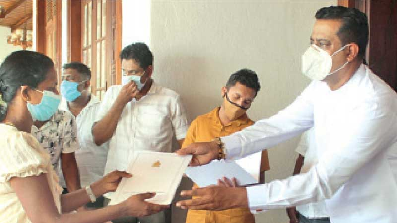 State Minister Sanath Nishantha presenting an appointment letter to a job recipient.