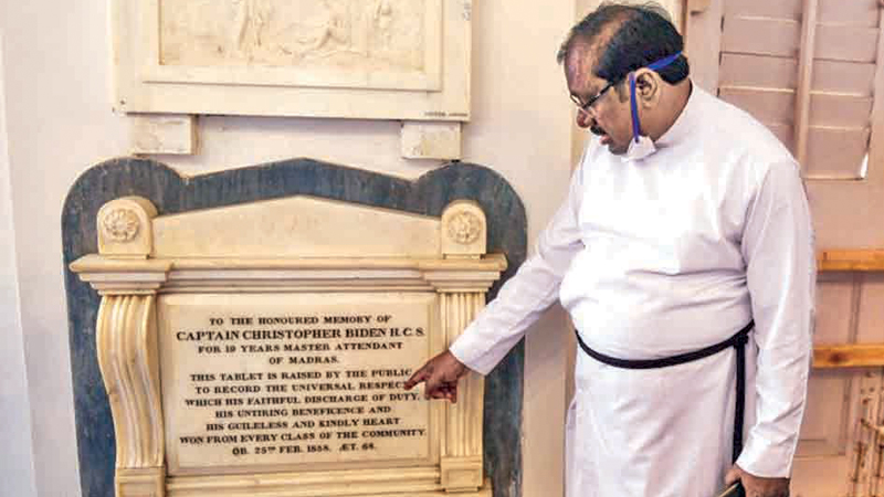 A pastor shows a memorial tablet for Christopher Biden, born in 1789, at St George's Cathedral in Chennai.