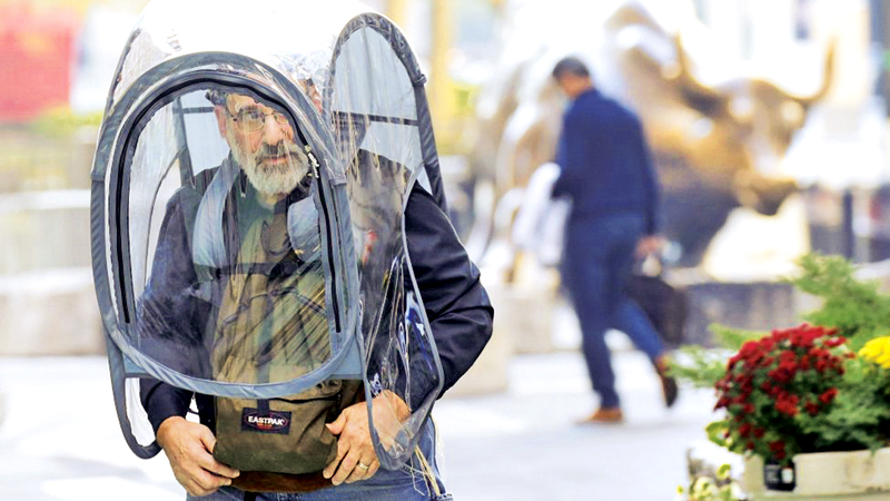 A man wears a personal bubble shield as he walks in New York City on Monday as the US surpassed 11 million COVID-19 cases on Sunday.