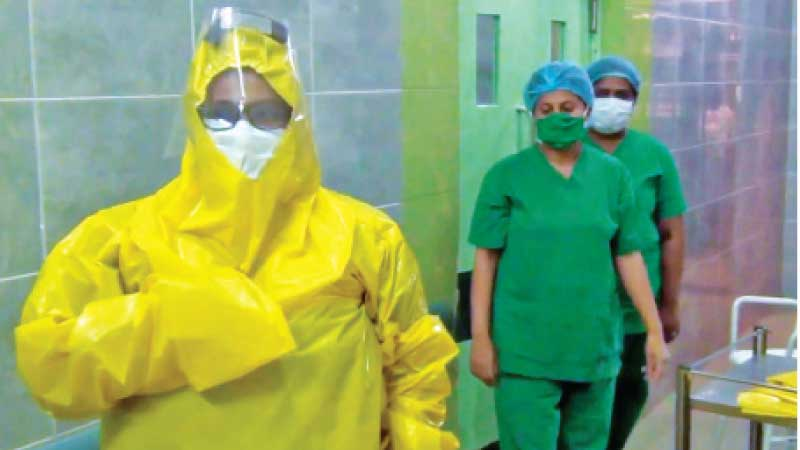 Health workers prepare to treat a COVID-19 patient