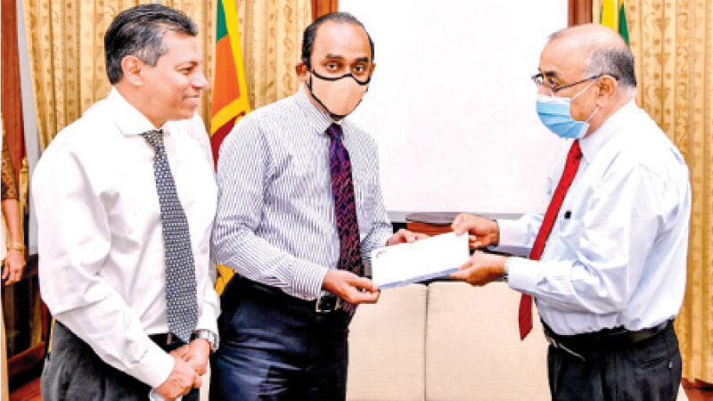 Chairman of People's Bank and People's Leasing Sujeewa Rajapakse accompanied by former CEO/GM Sabry Ibrahim donating Rupees Five Million to Dr P B Jayasundara, Secretary to Hon. President.