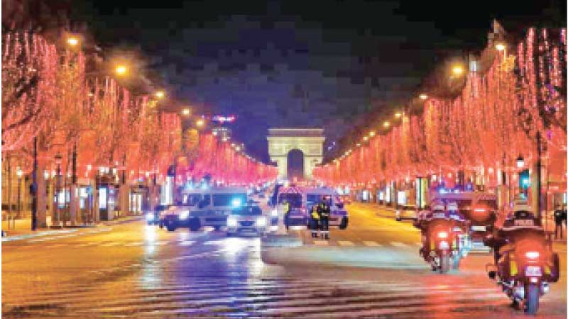 Policemen patrol on the Champs Elysees avenue on Sunday during the 8 p.m.- 6 a.m. curfew that is implemented in France to avoid a third wave of COVID-19 infections in Paris. - AFP