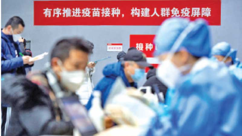 People submit forms to receive the COVID-19 vaccine at a makeshift vaccination site in Beijing's Chaoyang district, China January 3, 2021.