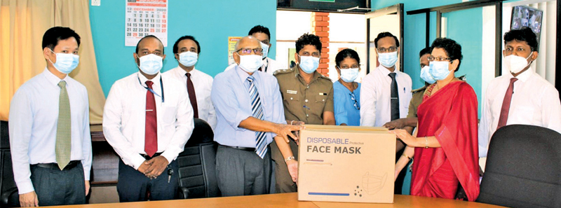 Tissa Wickramasinghe, COO of HIPG handing over 2000 surgical masks to the Regional Director of Health services while other staff members look on.