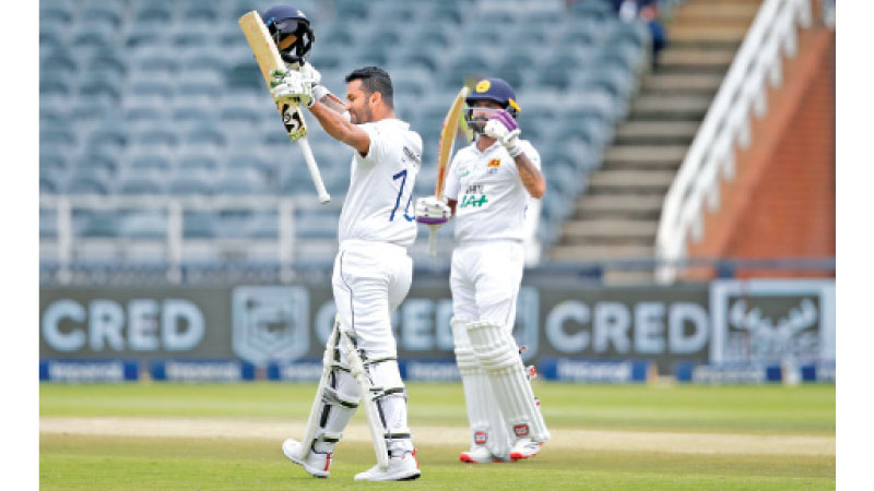 Sri Lanka's captain Dimuth Karunaratne (L) celebrates after scoring a century (100 runs) as Sri Lanka's Niroshan Dickwella (R) looks on during the third day of the second Test cricket match between South Africa and Sri Lanka at the Wanderers stadium in Johannesburg on January 5. AFP