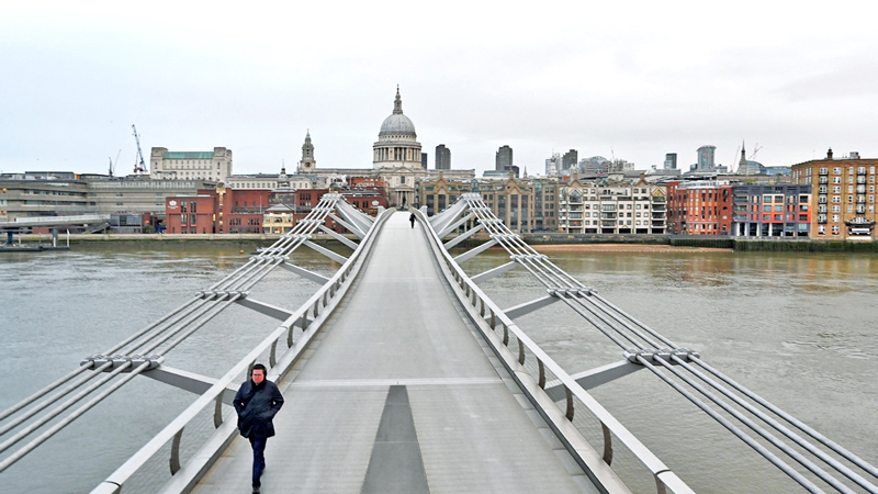 A pedestrian walks across a deserted Millennium Bridge as Britain entered another six-week lockdown in London on Tuesday. - AFP