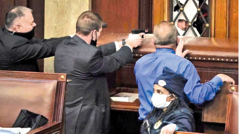 Federal agents draw their guns at the insurgents trying to break through a window of the Capitol Chamber.