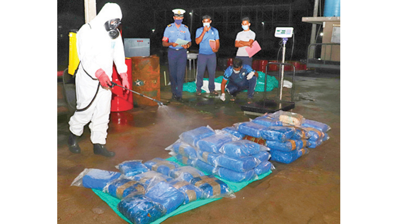 Navy personnel sanitising the sacks of Kerala cannabis in keeping with COVID-19 health guidelines.