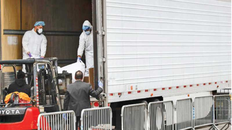 A body wrapped in plastic is loaded onto a refrigerated container truck used as a temporary morgue by medical workers wearing personal protective equipment due to COVID-19 concerns.