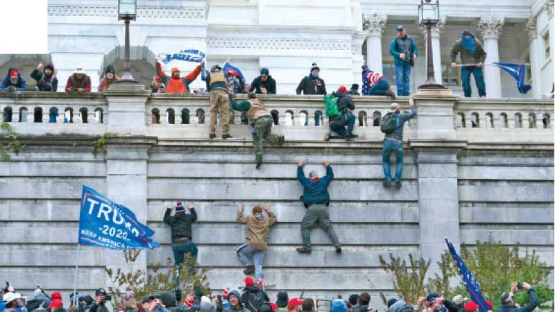 Supporters of President Donald Trump climb the west wall of the U.S. Capitol on Wednesday, January 6, 2021, in Washington.