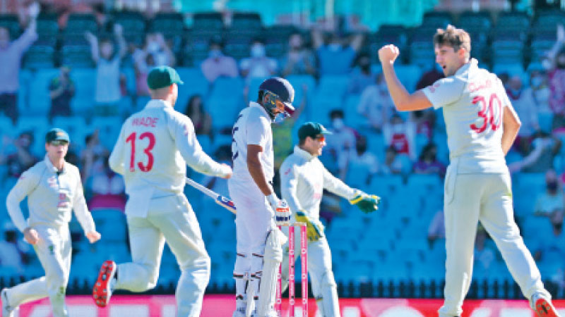 Australia's Pat Cummins (R) celebrates after taking the wicket of India's Rohit Sharma (C). AFP