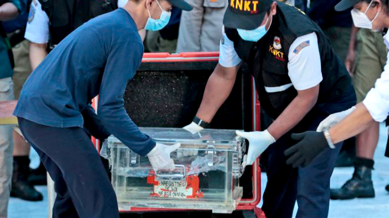 Members of National Transportation Safety Committee place a box containing the flight data recorder of Sriwijaya Air flight SJ-182 retrieved from the Java Sea.- AFP