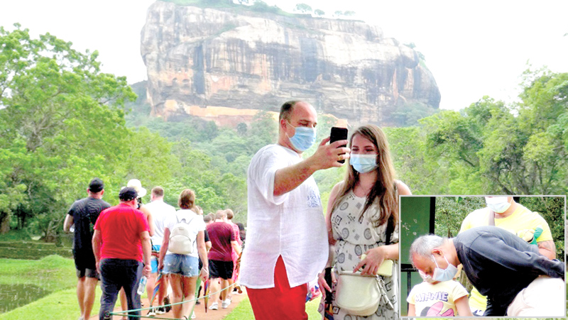 A group of Ukrainian tourists visited the Sigiriya Fortress yesterday under the Government's Pilot Project to revive the tourism industry affected by the COVID-19 pandemic. Picture shows a Ukrainian tourist taking a selfie with his friend. (Inset) Former Sri Lankan Envoy to Moscow Udayanga Weeratunga giving an ear to a Ukrainian child who was among the touring group. Pictures by Kanchana Ariyadasa, Sigiriya Group Corr.