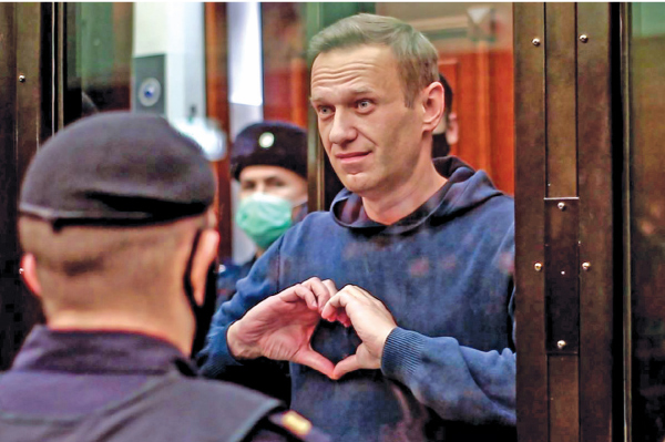 This screen grab from a handout footage provided by the Moscow City Court press service shows Russian opposition leader Alexei Navalny, charged with violating the terms of a 2014 suspended sentence for embezzlement, gesturing a heart shape from inside a glass cell during a court hearing in Moscow on Tuesday. - AFP
