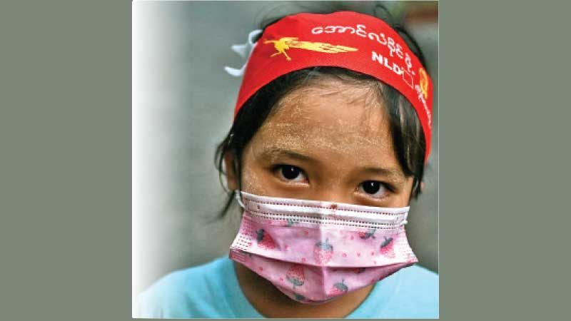 A young supporter of Aung Sang Suu Kyi's National League for Democracy (NLD) party wears a face mask and headband during a protest in Yangon, Myanmar on Friday. - AFP