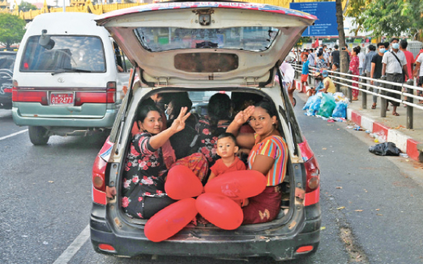 Women sitting in the back of a car hold up the three finger salute during a demonstration against the military coup in Yangon on Sunday. - AFP