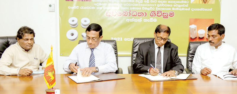 Cane, Brass, Clay Furniture and Rural Industry Promotion State Minister Prasanna Ranaweera and Wildlife Conservation Protection Programmes including Electric Fence and Trench Construction and Re-Forestation and Wildlife Resources Development State Minister Wimalaweera Dissanayake at the signing ceremony.