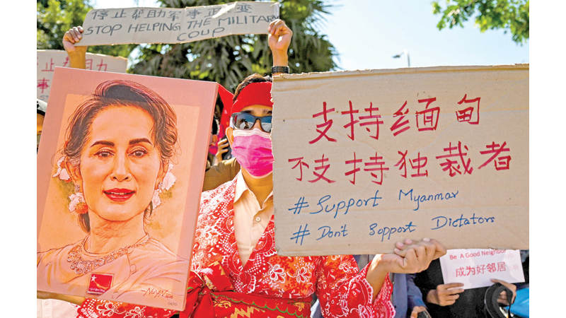 A protester hold up a painting of Aung San Suu Kyi and a sign during a demonstration against the military coup in Yangon on Thursday. - AFP