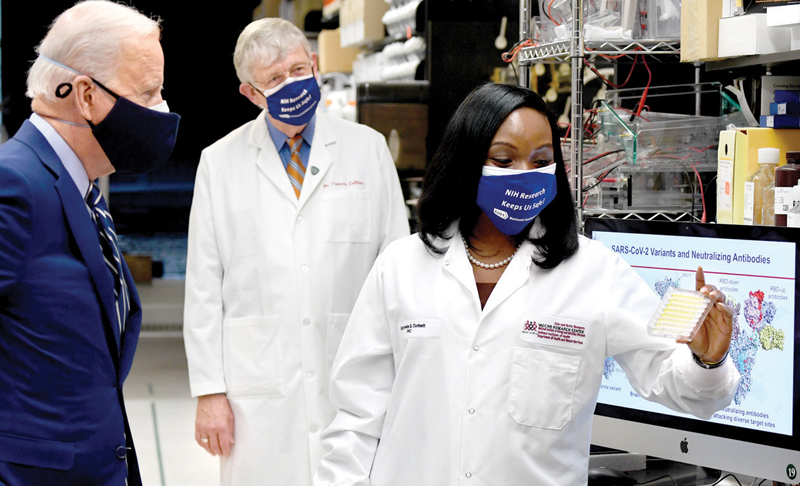 US President Joe Biden (L) listens to Dr. Kizzmekia S. Corbett (R) when he toured the Viral Pathogenesis Laboratory at the National Institutes of Health (NIH) in Bethesda, Maryland on Thursday.  White House Chief Medical Adviser on COVID-19 Dr. Anthony Fauci is at Centre.- AFP