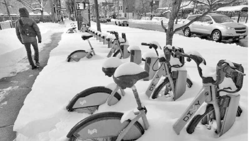 Bicycles are covered in snow in Chicago, Illinois on Tuesday as a result of the cold sweeping in the US. - AFP