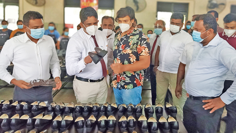 Prime Minister's Private Secretary, Rohitha Rajapaksa, Project Designer and Coordinator Prabath Ariyaratne, Managing Director Rohan Perera and CFO Suranga Sampath from The Lover and other officials at the shoe production facility in Giribawa.