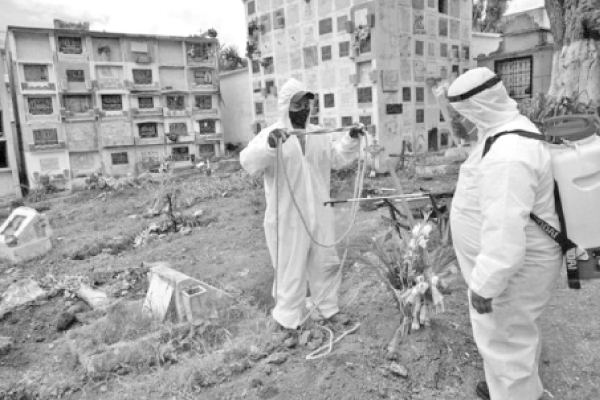 Gravediggers wearing biosafety suits disinfect a rope used to bury a coffin containing  a COVID-19 victim in Mexico.